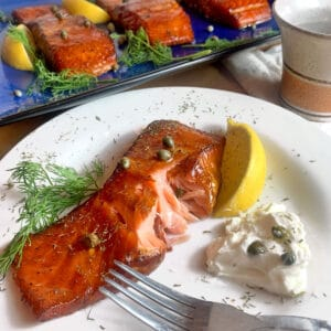 A plate of smoked salmon with cream cheese and capers.