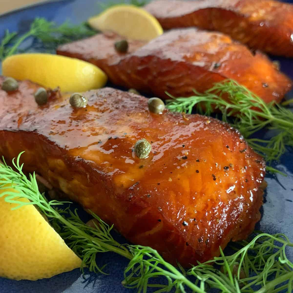 A bunch of salmon pieces garnished with fresh dill, lemons, and capers.