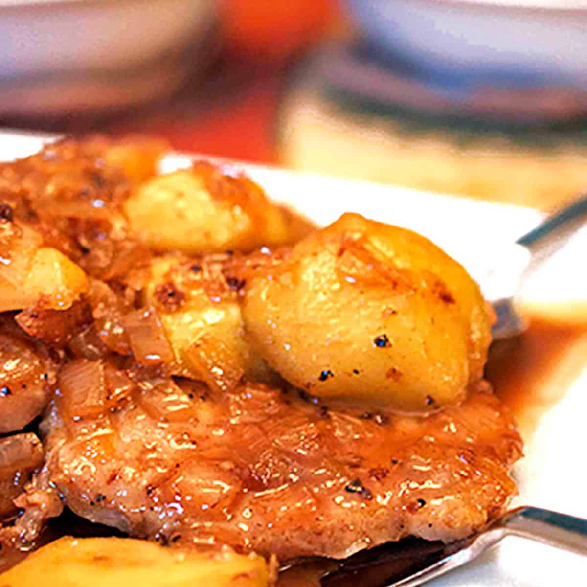 A cooked pork chop with a slice of apple.