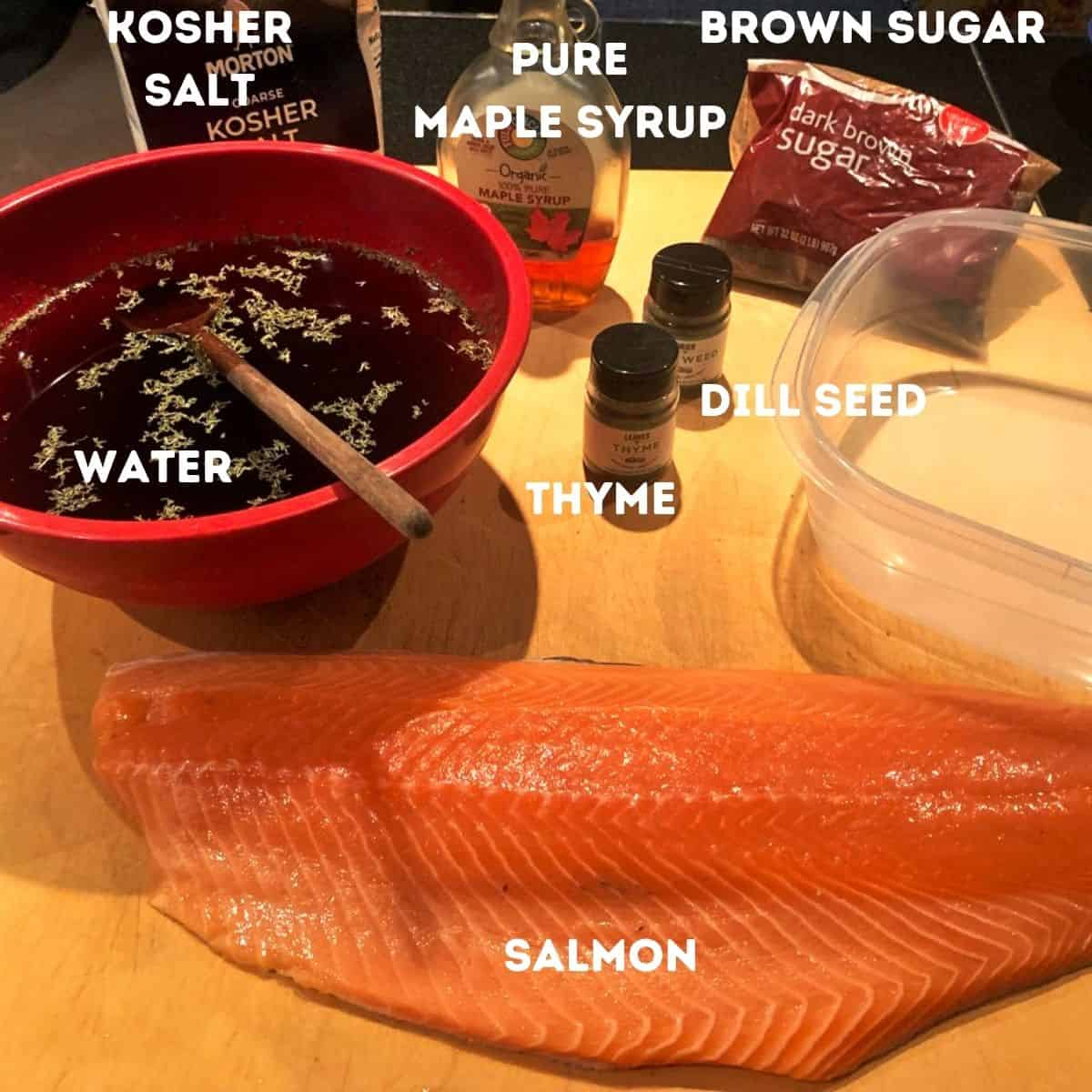 Salmon and other ingredients on a cutting board.