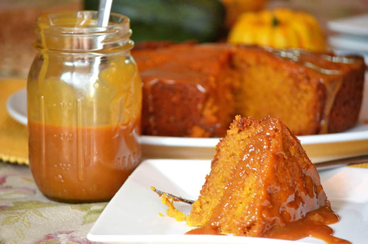 A pumpkin cake with a jar of caramel sauce.