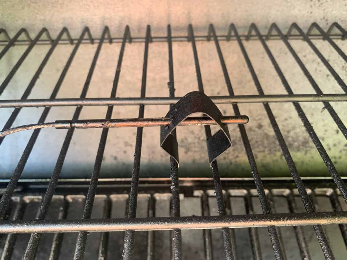 A temperature probe attached to the inside of a smoker.
