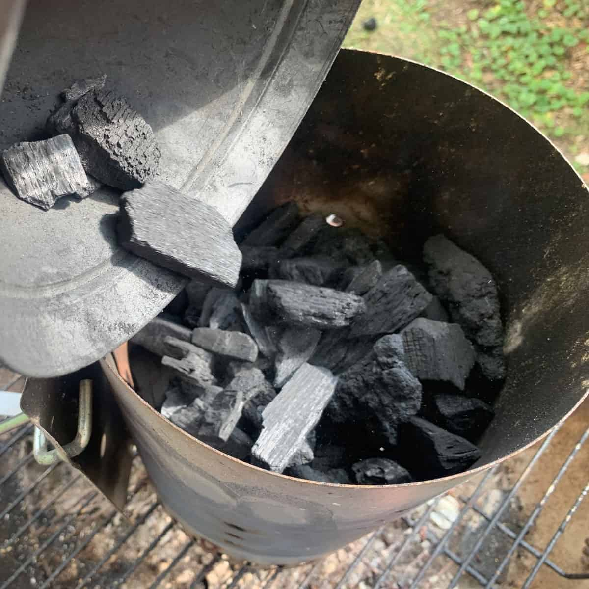 Dumping lump charcoal into a charcoal chimney.