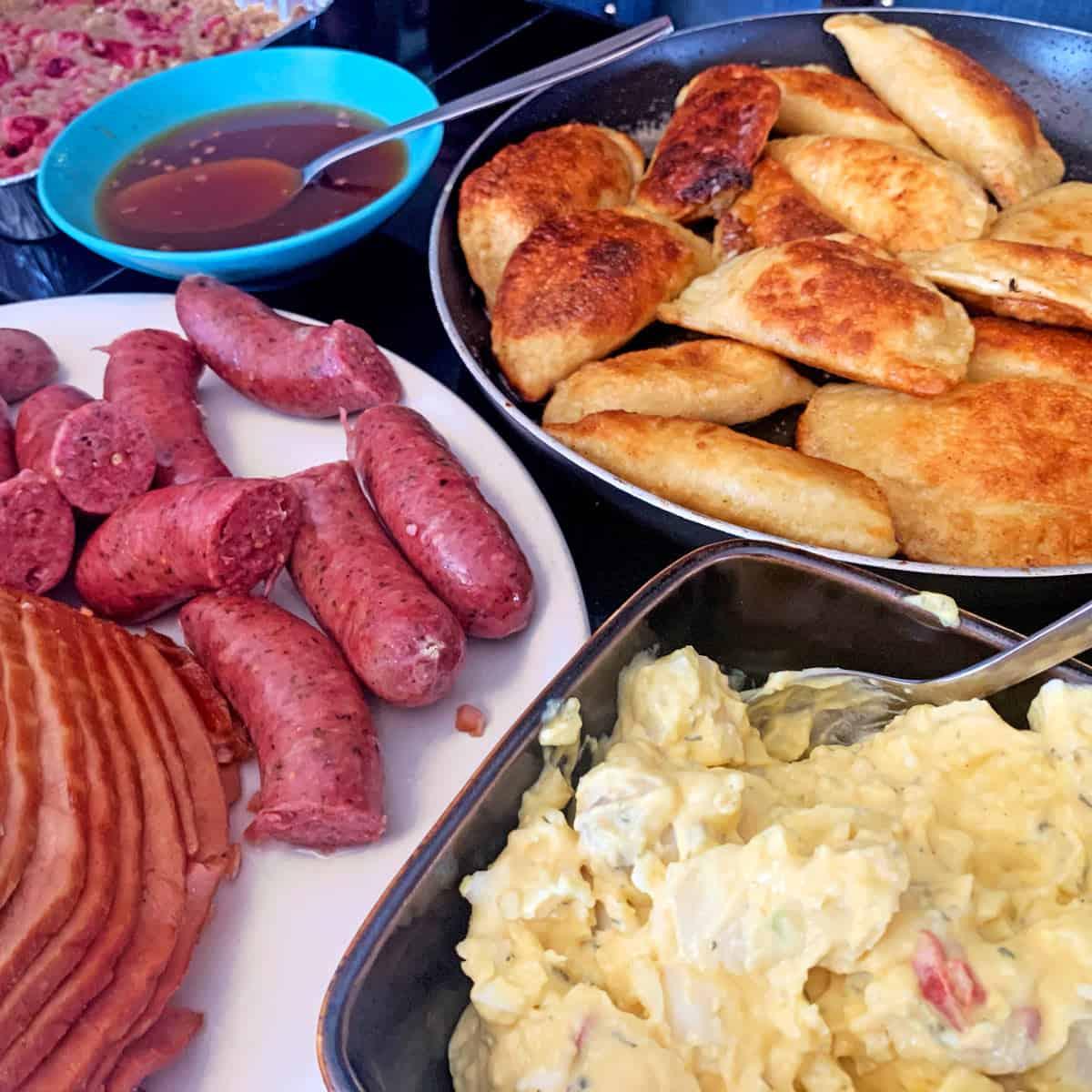 A pan of pierogies with Polish sausage and potato salad and ham.